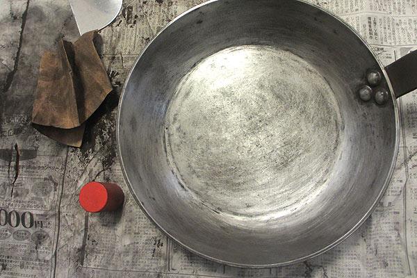 焦げを削り取った鉄のフライパンをヤスリがけする